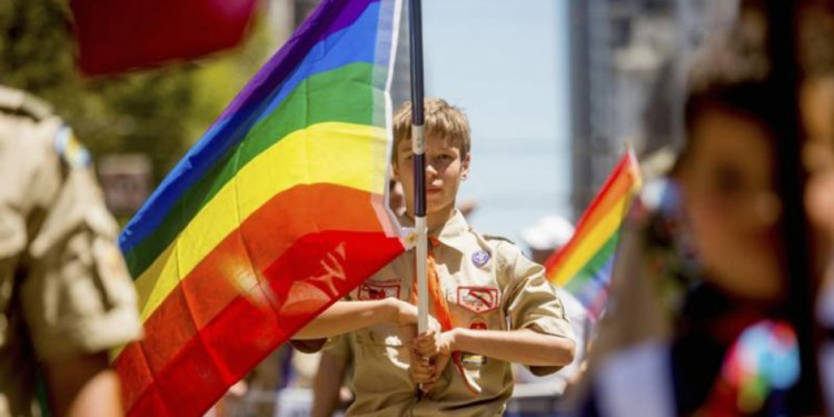 A Boy Scout carries a rainbow